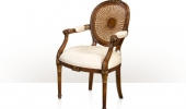 A hand carved and gilt armchair with a caned spoon back